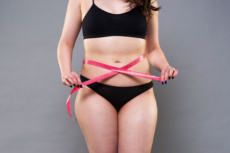 Photo pour Woman with fat belly, overweight female body on gray background, diet concept - image libre de droit