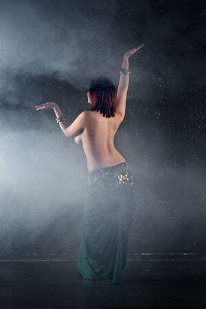 Foto de Sexy women performs belly dance in ethnic dress on dark smoky background, abstract art photography, studio shot - Imagen libre de derechos