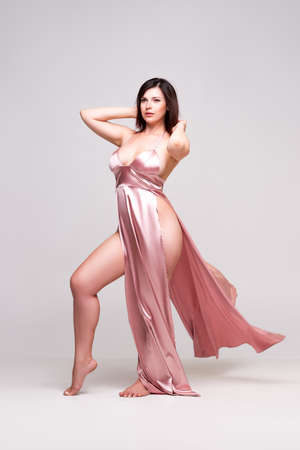 Photo pour Sexy woman in pink dress with deep neckline in studio on gray background. - image libre de droit