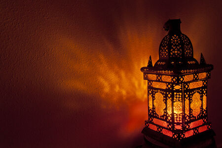 Moroccan lantern with gold colored glass illuminating colored patterns on wall