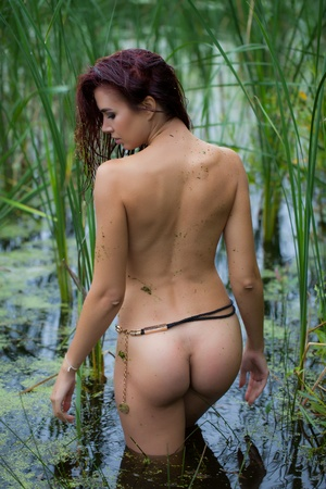 Foto de a naked young woman stands with her back on a swamp in a thicket of creeper with wet hair - Imagen libre de derechos