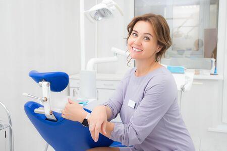 Foto de Young beautiful woman dentist smiling while sitting in medical office - Imagen libre de derechos