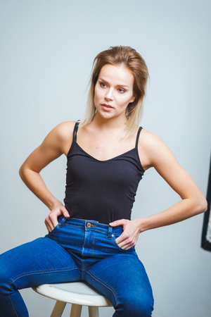 Photo pour Model tests. Photo session model in studio. Simple attractive portraits for a young beautiful girl in an empty room. Snaps. Attractive girl in jeans,  black shirt. Cheerful girl sitting on a bar stool - image libre de droit