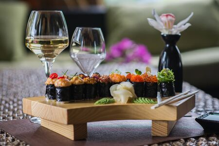 Photo pour Set of several different rolls on a wooden stand on a table in a Japanese restaurant. Japanese traditional sushi and rolls. Sea products. Beautiful table setting with flowers and wine in glasses. - image libre de droit