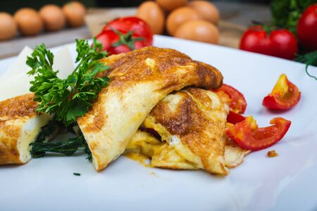 Photo pour Traditional omelet with vegetables, spinach, tomatoes and herbs on a wooden table in a restaurant. Classic european breakfast. Fried eggs with milk and cheese. Soft focus. - image libre de droit