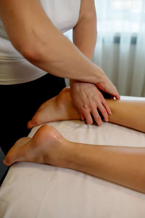 Massage therapist in a beauty salon giving a young woman a stone massage to relax the body and drain the lymph