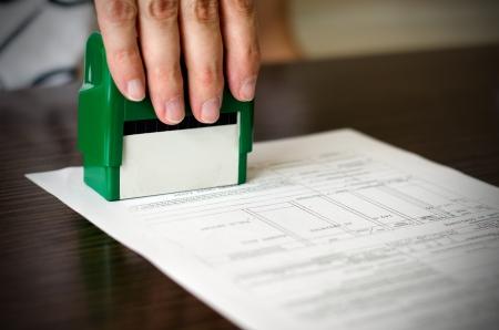 Photo pour Male hand pressing rubber stamp on document. Dark desktop underneath - image libre de droit