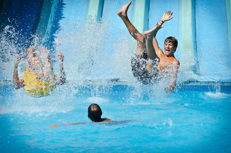 Foto de Young people having fun on water slides in aqua park, splashing into swimming pool - Imagen libre de derechos