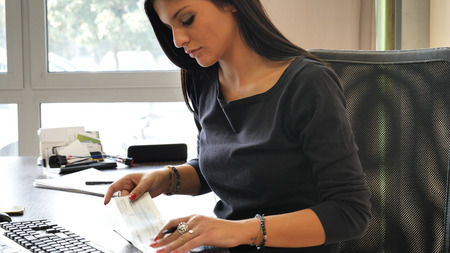 Foto de Female office worker writing and signing check or cheque, while sitting at her desk and looking at computer screen - Imagen libre de derechos