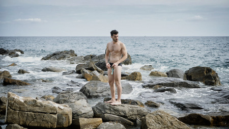 Photo pour Attractive fit athletic young man soaking in the sun at rocky beach in front of the sea, shirtless - image libre de droit
