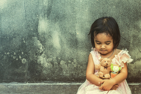 Photo for Girls sit hugging teddy side wall of the old. - Royalty Free Image