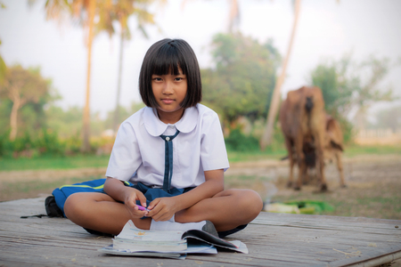 Asian girl of student dress doing homework in countryside.