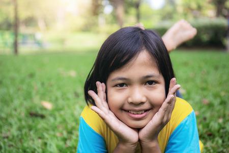 Photo pour Asian girls are smiling happily on the lawn. - image libre de droit