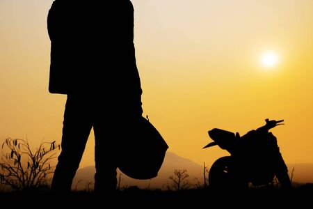 Photo pour Man are standing holding helmet carrying a motorcycle with silhouette. - image libre de droit