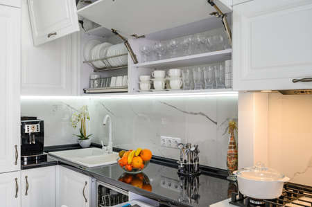 Foto de Luxurious white modern kitchen interior, drawers pulled out, doors open - Imagen libre de derechos