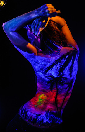 Girl with landscape bodyart in blacklight studio shot