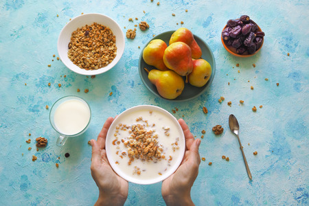 Muesli in a plate that hold women's hands on a blue background. Granola with pears.