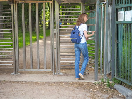 Turnstile, restricted entry. A lady travels through a turnstile to a private park