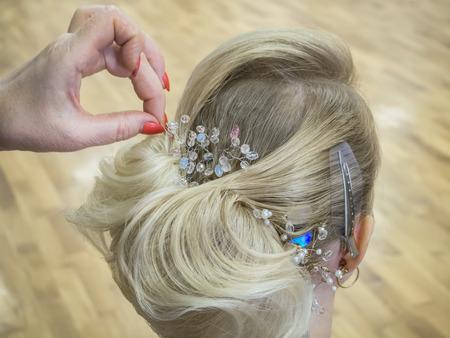 Foto de Hair stylist makes the bride a wedding hairstyle with hair detail accessory, closeup rear view - Imagen libre de derechos