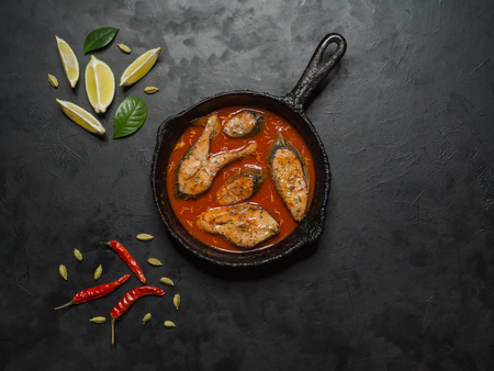 Foto de Top view of spicy and hot Bengali fish curry. Indian food. Fish curry with red chili, curry leaf, coconut milk. Asian cuisine. - Imagen libre de derechos