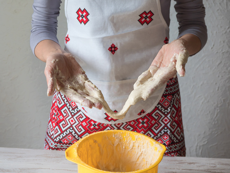 Foto de Bad dough. Kitchen disaster and bad cooking concept. Upset woman keeps sticky dough - Imagen libre de derechos