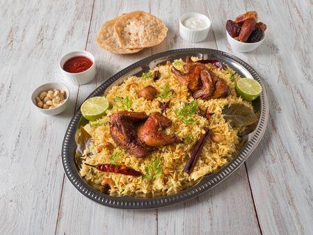 Photo pour Chicken Mandi with dates on a wooden table. Arabic cuisine. Top view. - image libre de droit