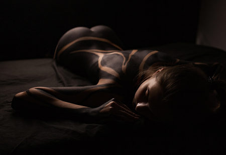 Photo pour Beautiful young girl with painted body lies on bed. Body art. - image libre de droit