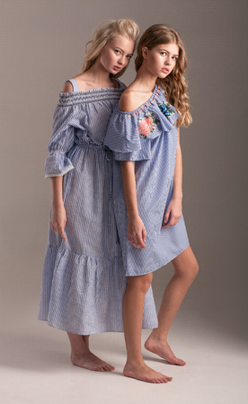 Two barefoot models in blue dresses with lace are posing in studio on gray background.