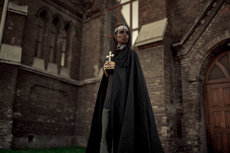 Photo for Beautiful young nun in black cassock, cloak and transparent cape is standing with cross in her hands on temple background. - Royalty Free Image