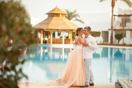 Foto de Happy newlyweds stand and hug on the villa next to the swimmimg pool during the honeymoon in Egypt. - Imagen libre de derechos