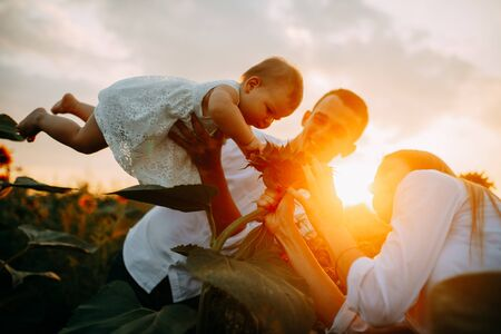 Photo pour Happy young family with baby has a fun and plays in the sunflower field at sunset. - image libre de droit