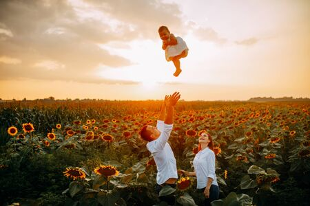 Photo pour Happy young parents with baby have a fun, play and throw up their baby in the sunflower field at sunset against sky background. - image libre de droit