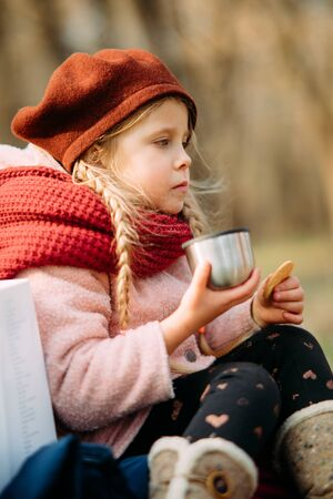 Photo for Girl drinks hot tea with a thermos and eats cookies while walking in the forest. - Royalty Free Image
