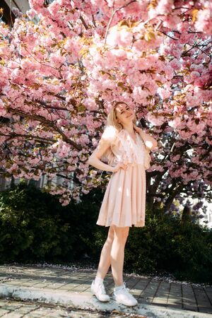 Photo for Young woman walks and enjoys in park with blooming sakura trees. - Royalty Free Image