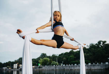 Photo pour Child girl aerialist performs gymnastic split on hanging aerial silk against background of river, sky and trees. - image libre de droit