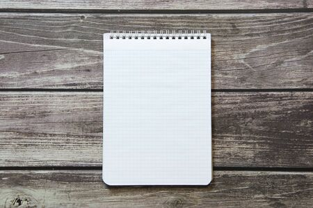 Photo for Notepad with a blank white sheet in a checker paper lies on the background of wooden boards - Royalty Free Image