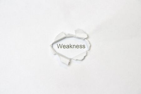 Word weakness on white isolated background, the inscription through the wound hole in the paper. Stock photo for web and print with empty space for text and design.