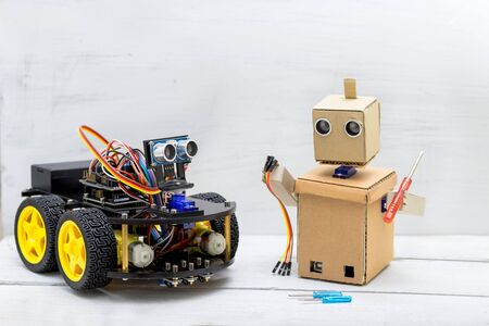 two robots are on the table, the robot is repairing another robot