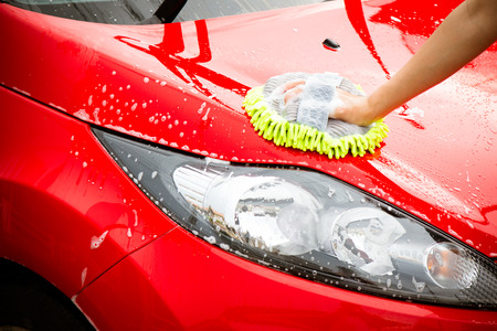 Photo pour Close-up Of Hand With green Brush Washing Red Car - image libre de droit
