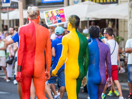 BARCELONA, SPAIN - JUNE 27, 2015: Three men creating the gay flag with their painted bodies during Gay pride parade in Barcelona, Catalonia, Spain