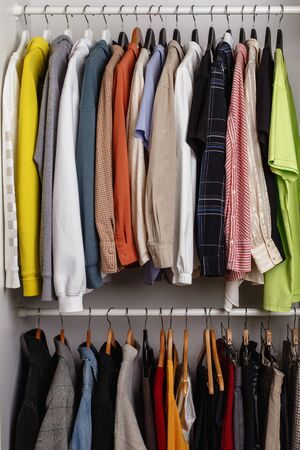 Photo pour Front view of clothes hung on hangers in the dressing room on the white bar - image libre de droit