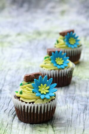 Three chocolate cupcakes decorated with icing and flowers