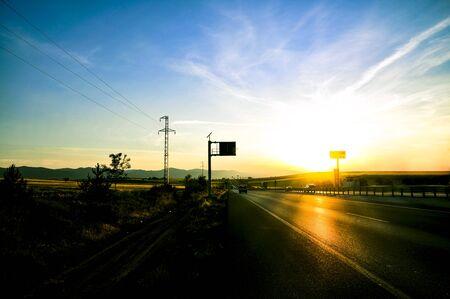 Photo pour Asphalt road and mountains with foggy nature landscape at sunset. - image libre de droit