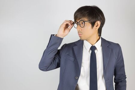 Photo for Young Asian Portrait Businessman in Navy Blue Suit Touch Eyeglasses and Look Beside on Grey Background - Royalty Free Image