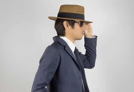 Photo for Young Asian Portrait Businessman in Navy Blue Suit Wear Sunglasses and Touch Hat Brim at Side View Pose on Grey Background - Royalty Free Image