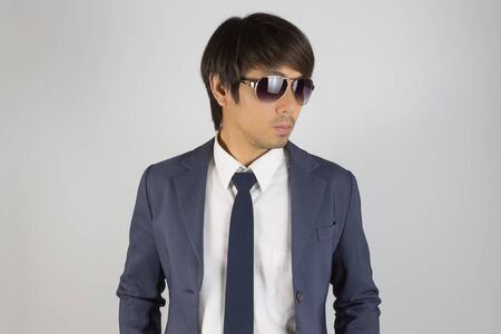 Photo for Young Asian Portrait Businessman in Navy Blue Suit Wear Sunglasses and Look Beside on Grey Background - Royalty Free Image
