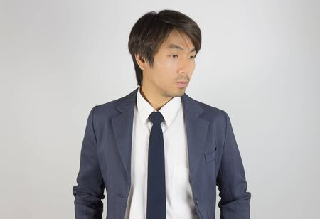 Photo for Young Asian Portrait Businessman in Navy Blue Suit Looking Below on Grey Background - Royalty Free Image
