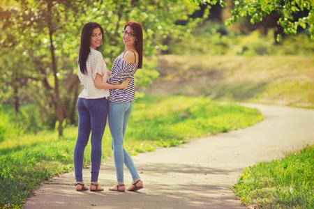 Girlfriends in the park, two young women walking in the walkway