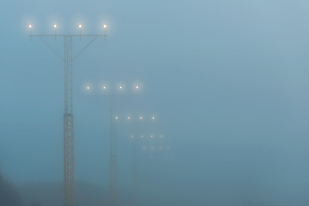 Landing lights at a airport during foggy weahter, help airplanes find the runway approach