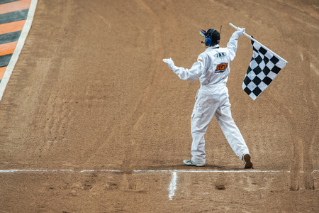 STOCKHOLM - SEPT 26, 2015: Referee with a chequered flag at the finish line at TEGERA Stockholm FIM Speedway Grand Prix at Friends Arena in Stockholm.